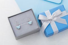 Butterfly shape earrings in gift box on blue background with cop. Y space. Cute jewelry for child girl. Present for birthday Royalty Free Stock Photo