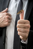 Butterfly sitting on businessman's thumb Royalty Free Stock Images