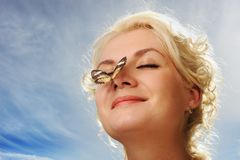 Butterfly sitting on a woman nose royalty free stock photos