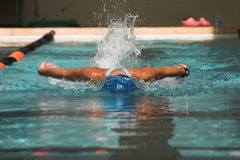 Butterfly stroke. Powerful female swimmer swimming butterfly stroke Royalty Free Stock Images