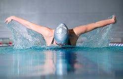 Butterfly stroke. Woman swims using the butterfly stroke in indoor pool