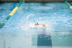 Butterfly stroke at swim meet. A swimmer swims the butterfly stroke at a swim meet. The motion is blurred showing movement through the water Royalty Free Stock Photos