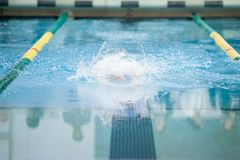 Butterfly stroke at swim meet. A swimmer swims the butterfly stroke at a swim meet. The motion is blurred showing movement through the water Stock Photos
