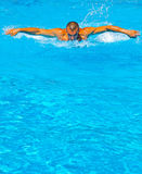 Butterfly swimmer. Young athletic man working out swimming in pool Royalty Free Stock Images