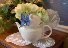 Butterfly Teapot. Teapot displayed decoratively on a butterfly mat with a blue butterfly attached t pot Stock Images