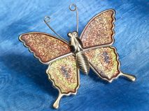 Butterfly trinket on blue fabrics Stock Photos