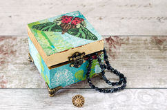 Butterfly Trinket Box. A beautiful hand made trinket box decoupaged in vintage papers and gilded with gold leaf, on a shabby chic background Stock Images