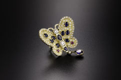 Butterfly yellow gold ring. With diamonds, sapphires and rubies on black background Royalty Free Stock Images