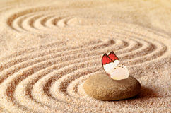 Butterfly on a zen stone with circle in the sand. Royalty Free Stock Image