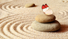 Butterfly on a zen stone with circle in the sand. Royalty Free Stock Photos