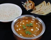 Butterhühnercurry mit Basmatireis und indischem Brot mit schwarzem Hintergrund stockfotos