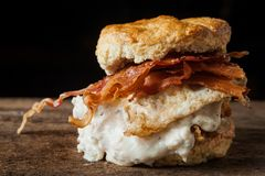 Buttermilk biscuit and fried chicken breast sandwich with a frie. D egg and bacon on dark rustic background Royalty Free Stock Images