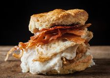 Buttermilk biscuit and fried chicken breast sandwich with a frie. D egg and bacon on dark rustic background Royalty Free Stock Photos