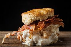 Buttermilk biscuit and fried chicken breast sandwich with a frie. D egg and bacon on dark rustic background Stock Photo