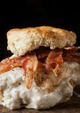 Buttermilk biscuit and fried chicken breast sandwich with a frie. D egg and bacon on dark rustic background Stock Images