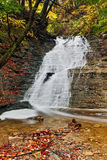 Buttermilk Falls in Autumn. Beautiful Buttermilk Falls, a waterfall in Ohio's Cuyahoga Valley National Park, cascades down over rock ledges with colorful autumn Royalty Free Stock Photos