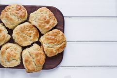 Buttermilk Southern Biscuits on Cutting Board Over White Table. Fresh buttermilk southern biscuits or scones over a white table shot from above. Top view royalty free stock images