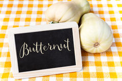 Butternut squash on a chequers tablecloth and a slate. With Word Butternut Royalty Free Stock Image