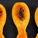 Butternut squash piece with pumpkin seeds on black background Royalty Free Stock Images