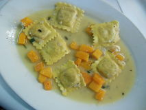 Butternut squash ravioli at Italian restaurant. Gourmet butternut squash ravioli, a gourmet Italian food dish on a white plate at an upscale restaurant. This Royalty Free Stock Photo