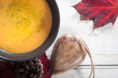 Butternut squash and sweet potato soup. Bowl of butternut squash and sweet potato soup served on a white table top with autumn leaves, pine cone and wooden table Stock Images