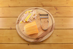Butternut squash with a vegetable peeler on a chopping board Stock Photography
