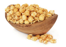 Butterscotch Popcorn. In an olive wood bowl and loose over white background royalty free stock image