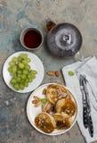 Butterwochen-Festivalmahlzeit Shrovetide Maslenitsa Stapel von Pfannkuchen Blini mit Karamell mit Nüssen, grüne Traube, Tee schli stockfotos
