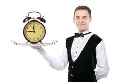 Buttler holding a silver tray. With a alarm clock on it royalty free stock photos