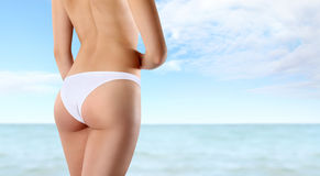 Buttocks and legs of slim woman isolated on sea summer backgroun Royalty Free Stock Images