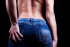 Buttocks of young woman in blue jeans. Portrait of buttocks of young woman Royalty Free Stock Images
