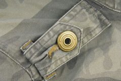 Button on camouflage jacket Stock Photos