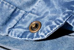 Button closure on a blue denim shirt. Shallow depth of field. Button closure on a blue denim shirt closeup. Shallow depth of field royalty free stock photo