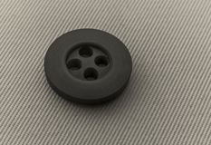 The button is dark gray. Button dark gray for the textile industry Stock Photography
