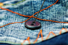 Button and jean. Needle and button on back pocket of jean Stock Image