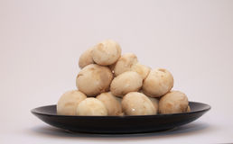 Button mushrooms. On a black plate, white background Stock Photos