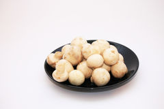 Button mushrooms. On a black plate, white background Stock Photography