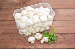 Button mushrooms in a plastic tray on a wooden surface Stock Photography