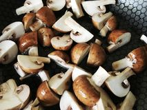 Button mushrooms sliced in a pan. Cooking at home, healthy and fun Stock Photos