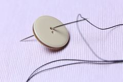 Button and needle. Ready for sew, white background, copyspace royalty free stock image