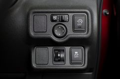Button panel with security option technology in car. Button panel in car with headlight level switch and traction control and idling stop and wing mirror royalty free stock images