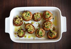 Button, portobello mushrooms stuffed with cheese and herbs. With olive oil in a baking dish Stock Photography