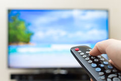 Button pressing on TV remote control royalty free stock photo
