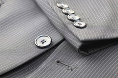 Button suit stripe. Four gray buttons sewn on the sleeve men's suit system Royalty Free Stock Image