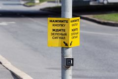 Button to switch the traffic signal on the pole. Yellow sign above the traffic light switch button. inscription in Russian: press the button wait for the green stock images