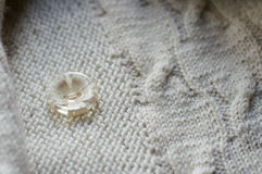 Button & white detail of woven handicraft knit sweater. Closeup on button & detail of woven handicraft knit woolen design texture. Fabric white background royalty free stock images