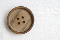 Button on a wooden table Stock Photo