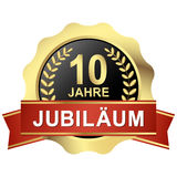 Button 10 years jubilee & x28;in german& x29;. Gold button with red banner for 10 years jubilee & x28;text in german& x29 Royalty Free Stock Photos