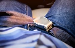 The buttoned belt on the passenger on the plane. Close up, sunrise light on it Stock Photo