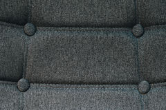 Buttoned chair back support detail. Gray fiber material texture Stock Photos
